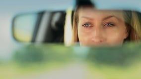 Reflexion av kvinnas blåa ögon i backspegel stock video