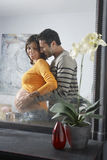 Reflexion av mannen som omfamnar gravida kvinnan Royaltyfri Foto
