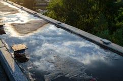 Reflexion av moln i en pöl på kanten av en oavslutad bro arkivfoto