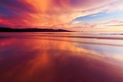 Reflexion av solnedgångfärger på en strand Arkivfoto