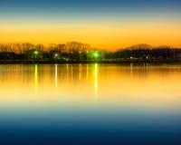 Reflexion av solnedgångglöd på parkeradammet Royaltyfri Fotografi