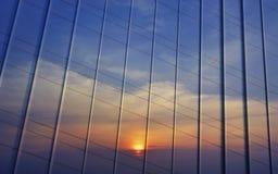 Reflexion av solnedgånghimmel i metallvägg Arkivfoto
