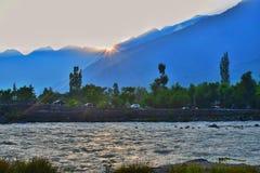Reflexion av solstrålar i vattnet Solnedg?ng i himalayasna Rent vatten som kör till och med den snabba strömmen royaltyfria foton