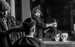 Reflexion of barber with clipper trimming hair of client. Hipster client getting haircut. Barber with hair clipper works. On haircut of bearded guy, barbershop royalty free stock photography