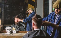 Reflexion of barber with clipper trimming hair of client. Hipster client getting haircut. Barber with hair clipper works. On haircut of bearded guy, barbershop stock image