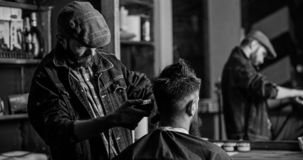 Reflexion of barber with clipper trimming hair of client. Hipster client getting haircut. Hipster lifestyle concept. Barber with hair clipper works on haircut royalty free stock photo