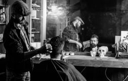Reflexion of barber styling hair of bearded client with comb. Hipster client getting hairstyle. Barbershop concept. Man. With beard and mustache in hairdressers royalty free stock images