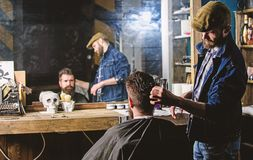 Reflexion of barber styling hair of bearded client with comb. Hipster client getting hairstyle. Barbershop concept. Man. With beard and mustache in hairdressers royalty free stock photography