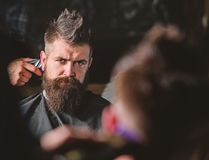 Reflexion of barbers hand with hair clipper trimming nape of client. Hipster bearded client getting hairstyle in front. Of mirror. Barber with hair clipper royalty free stock image