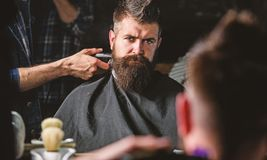Reflexion of barbers hand with hair clipper trimming nape of client. Hipster bearded client getting hairstyle in front. Of mirror. Barbershop concept. Barber royalty free stock images