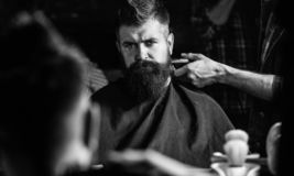 Reflexion of barbers hand with hair clipper trimming nape of client. Hipster bearded client getting hairstyle in front. Of mirror. Barbershop concept. Barber royalty free stock image