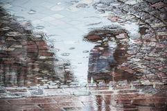 Reflexion of couple with umbrella on cobbles place. In the city stock photos
