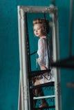 Reflexion in der bescheidenen schönen blonden Braut des Spiegels im weißen Negligé, das auf der schwarzen Schmiedeeisentreppe sit Lizenzfreie Stockbilder