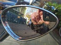 Reflexion der Hand mit Kamera im Rückspiegel Stockfotos