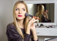 Reflexion der jungen Schönheit ihr Make-up anwendend lizenzfreies stockbild