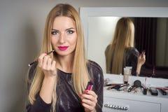 Reflexion der jungen Schönheit ihr Make-up anwendend, schauend in einem Spiegel lizenzfreies stockbild