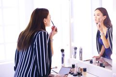 Reflexion der jungen Sch?nheit ihr Make-up anwendend, schauend in einem Spiegel stockbild