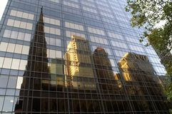 Reflexion der Kirche und einiger Gebäude in den Wolkenkratzerfenstern Lizenzfreie Stockbilder