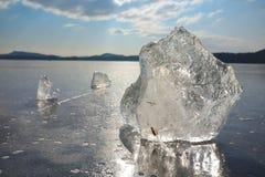 Reflexion der Sonne strahlt im flachen Eis auf dem See aus Luftblasen Stockbilder