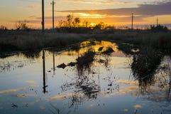 Reflexion der untergehenden Sonne in einer Pfütze auf einem Schotterweg auf dem russischen Gebiet Lizenzfreies Stockbild