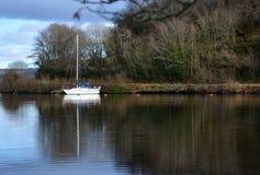 Reflexion der Yacht machte im Loch in Schottland fest Stockfotos
