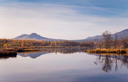 Reflexion des Berges im blauen Wasser Lizenzfreie Stockbilder