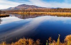 Reflexion des Berges und des Himmels im blauen Wasser Stockfotografie