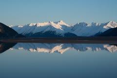 Reflexion des Berges und des Sees mit Schnee Stockbild