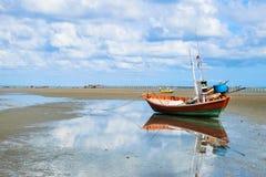 Reflexion des Fischerbootes auf Strand mit Anlegestellenhintergrund Lizenzfreie Stockfotos