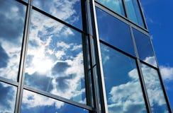 Reflexion des Himmels und der Wolken in den Fenstern des Gebäudes Lizenzfreie Stockbilder