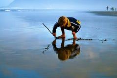 Reflexion des Jungen-Schreibens im Sand Stockfoto