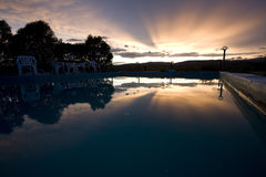 Reflexion des Sonnenuntergangs über Swimmingpool Stockbilder