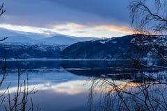Reflexion des Sonnenuntergangs und der Berge auf See stockfotografie
