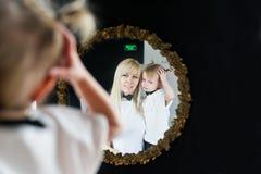 Reflexion in einem Spiegel der Mutter und ihrer kleinen Tochter Lizenzfreies Stockbild