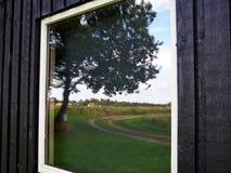 Reflexion eines Baums und Land versehen auf dem Fenster mit Seiten Stockfoto