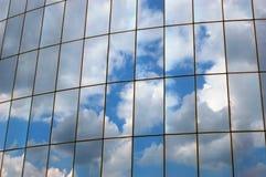 Reflexion eines bewölkten Himmels in der Glaswand Stockbilder