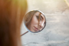 Reflexion eines schönen Mädchens in einem Motorrad blies Rearview MI Trübsal Stockfoto
