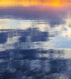 Reflexion för aftonhimmelfärger i sjöabstrakt begreppbakgrund Arkivbilder