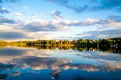 Reflexion för himmel och för moln för sommarsolnedgång evining i vatten Royaltyfria Bilder