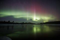 Reflexion för nordliga ljus på vatten i Lapland, Finland Arkivfoton
