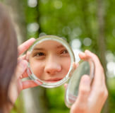 Reflexion face of girl. Lovely girl looks in round mirror against summer green park Stock Images