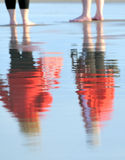 Reflexion of figures. Of two people on wet sand. Coast of the Baltic sea. Evening Stock Photos