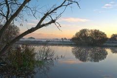 Reflexion från en vintersoluppgång över en flod Arkivfoto