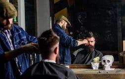 Reflexion fryzjer męski z cążki arymażu włosy klient Modnisia klient dostaje ostrzyżenie Fryzjer męski z włosianego cążki pracami Obrazy Royalty Free