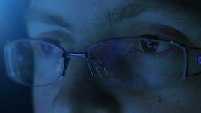 Reflexion i ögat och exponeringsglasen av bildskärmskärmen när kvinna som surfar internet lager videofilmer