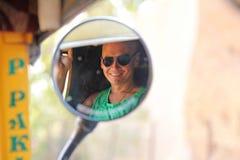 Reflexion i en rund spegel Den manliga framsidan reflekteras i spegeln av tuktuken En turist- man i solglasögon reflekteras royaltyfri bild