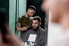 Reflexion i spegeln av en barberare som gör en hårklippning av ung stilfull man på en frisersalong arkivbild