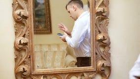Reflexion i spegeln den stiliga mannen, affärsman i en vit skjorta rymmer en smartphone, mobiltelefon Ung grabb arkivfilmer