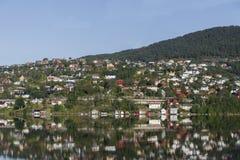 Reflexion i vattnet av den norska fjorden av färgrika hus Royaltyfria Foton
