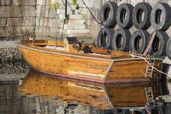 Reflexion i vattnet av ett förtöjt trämotoriskt fartyg Royaltyfri Foto